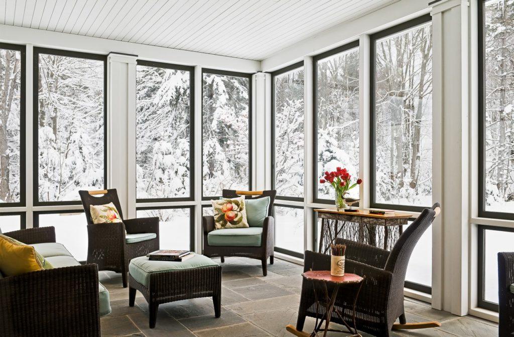 Farmhouse home restored barn sunroom black windows stone flooring