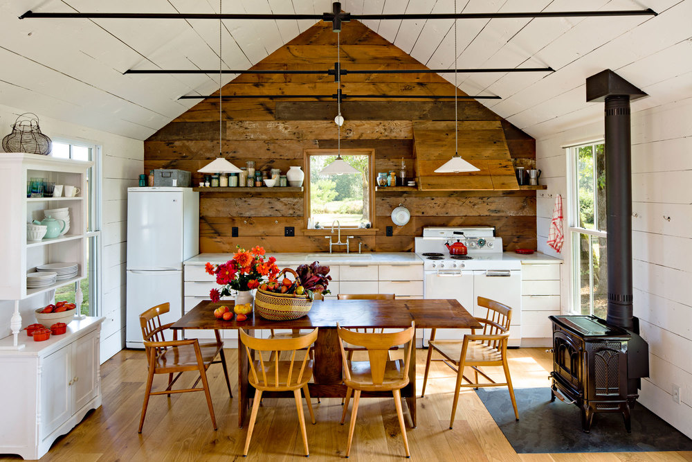 Tiny remodeled cottage kitchen living room dining room painted board walls ceiling wood burning stove