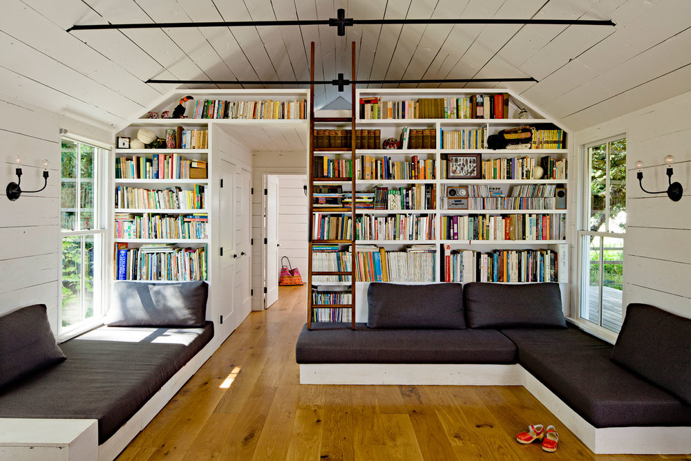 Tiny remodeled cottage family room built in bookcases built in sofa painted board walls ceiling wood burning stove