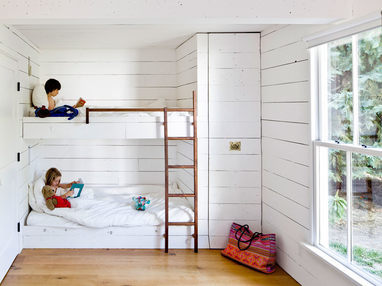 Tiny remodeled cottage bedroom built in bunk beds ladder painted board walls ceiling wood burning stove