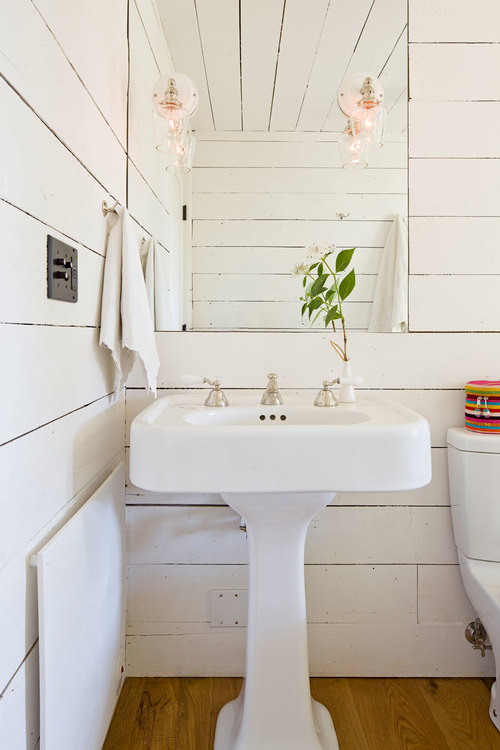 Tiny remodeled cottage bathroom pedestal sink painted board walls ceiling