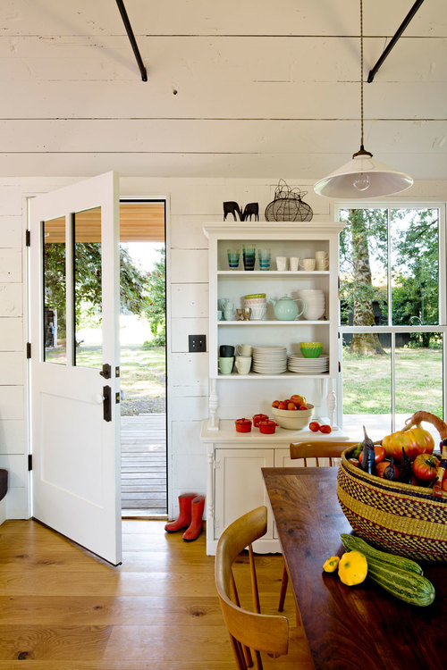 Tiny remodeled cottage dining room painted board walls ceiling built in shelving