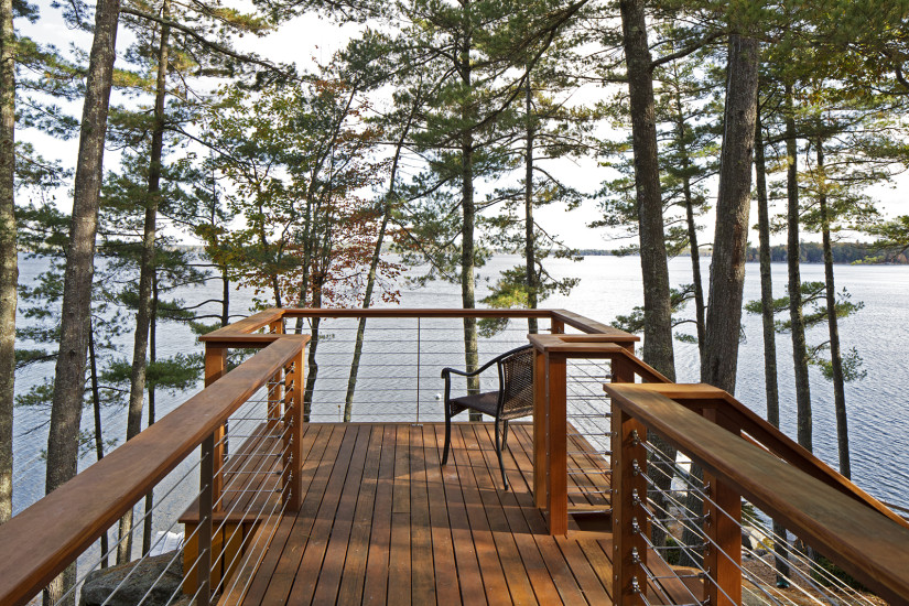 Contemporary lake house remodel wood deck cable railing