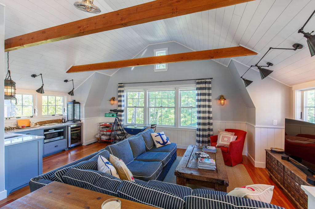 Seaside cottage family room exposed ceiling beams painted board walls ceiling wide plank flooring