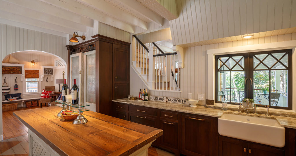 Seaside cottage kitchen marble countertops painted board walls farmhouse sink