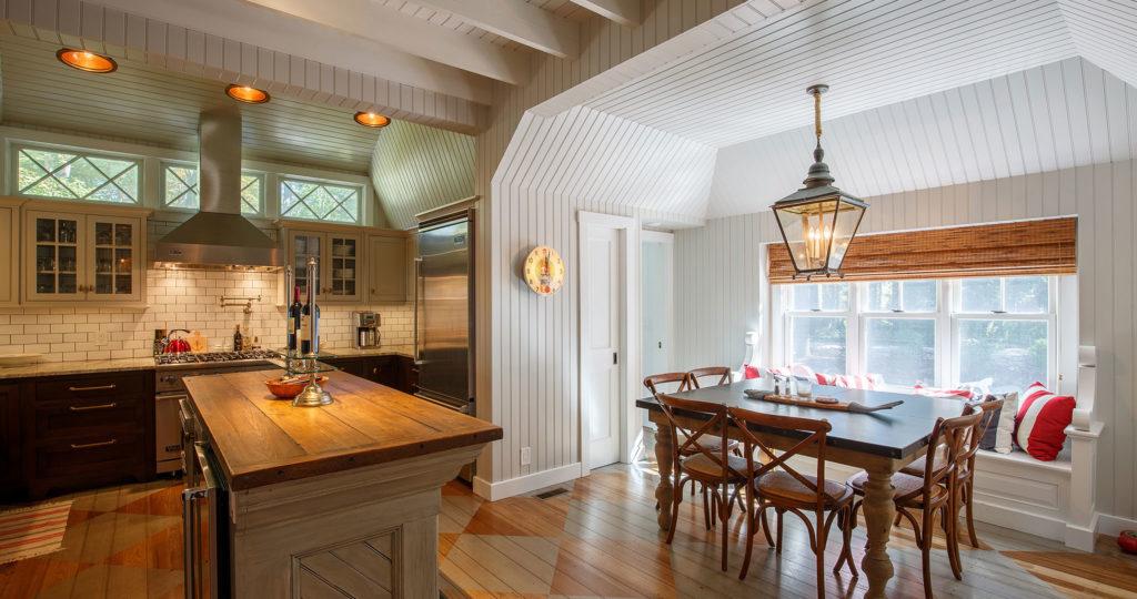 Seaside cottage kitchen dining room wide plank floors exposed ceiling beams wood countertop