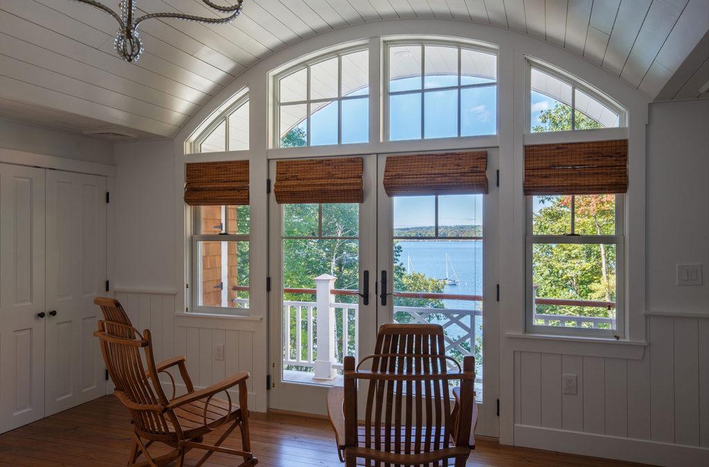 Seaside cottage master bedroom wide plank flooring arched window
