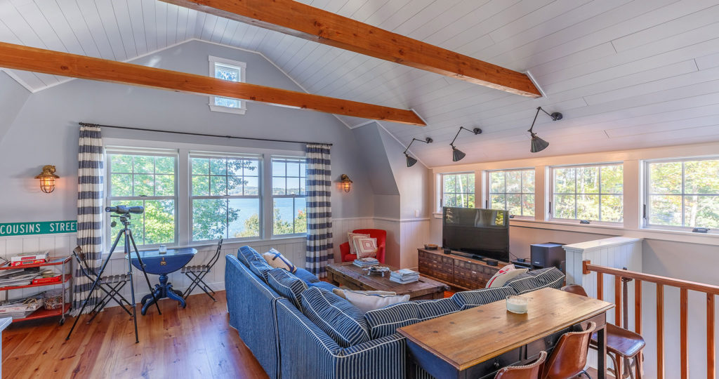 Seaside cottage family room exposed ceiling beams painted board walls and ceiling
