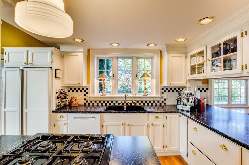 White Kitchen Dark Countertops Cooktop on Island